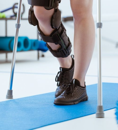 Injured patient in an orthotics leg brace exercising in a physiotherapy office